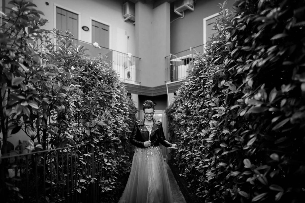 Black and white luxury photo of a bride walking between two hedges that are taller than she is and wearing a smile and a leather jacket as she leaves to arrive at her wedding in Italy, shot by luxury wedding photographer Francesco Bognin