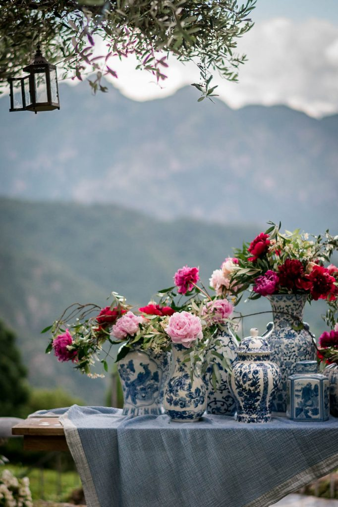 Lovely fuscia and pink flowers rest in blue and white cloisonné vases with the hills of the amalfi coast in the background, planned by Brenda Babcock and shot by luxury wedding photographer Francesco Bognin