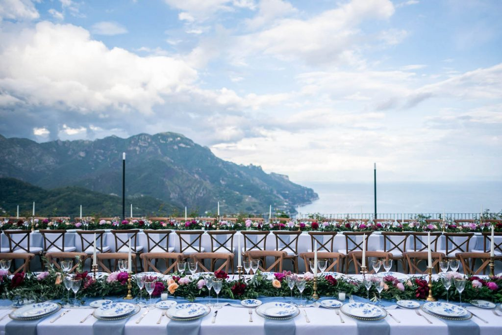 Lovely fuscia and pink flowers decorate a table of blue and white cloisonné for a pre-wedding tea ceremony showing the sea and hills of the amalfi coast at Belmond Hotel Caruso, planned by Brenda Babcock and shot by luxury wedding photographer Francesco Bognin