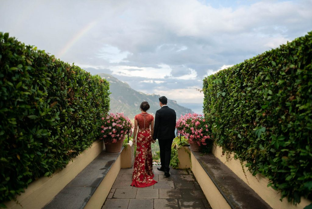 An asian bride and groom dressed for their tea ceremony andt sanding at the top of stairs looking out toward the hills and sea of Ravello on the Amalfi coast, with a rainbow overhead. Planned by Brenda Babcock and shot by luxury wedding photographer Francesco Bognin