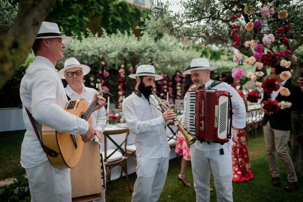 A set of lively musicians dressed in white and playing typical italian instruments with flowers and trees behind them at the Belmond Hotel Caruson in Ravello on the Amalfi Coast of Italy, planned by Brenda Babcock and shot by luxury wedding photographer Francesco Bognin