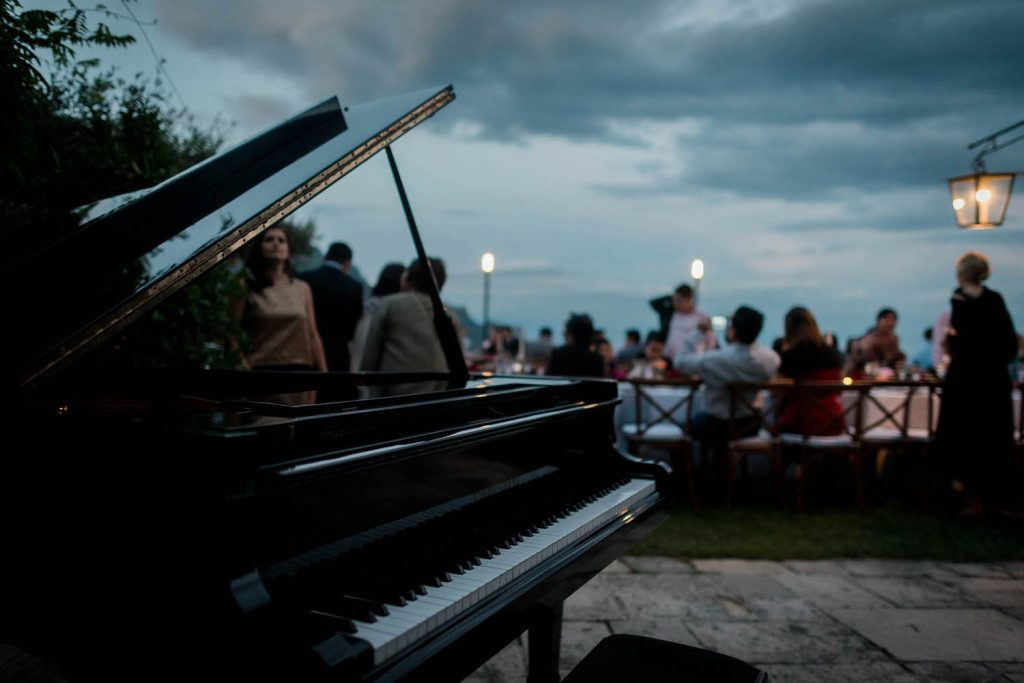A grand piano with guests and the amalfi coast in the background in Ravello at the Belmond Hotel Caruso, planned by Brenda Babcock and shot by luxury wedding photographer Francesco Bognin