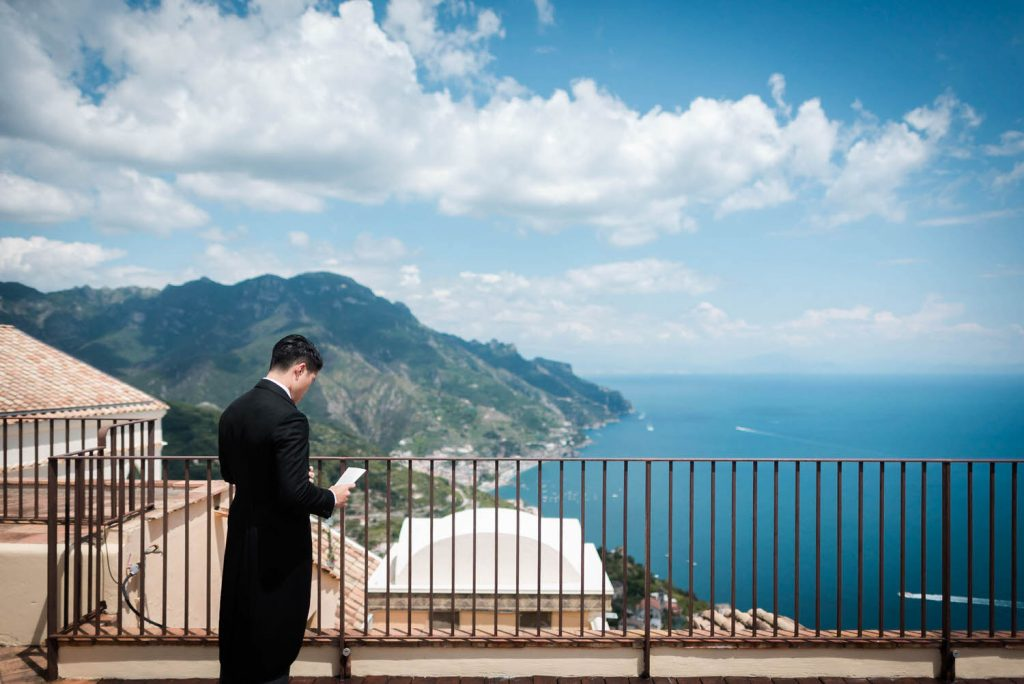 A groom takes a moment to review his speech standing at edge of a terrace overlooking the sea and hi9lls of the Amalfi Coast in Italy, at the Belmond Hotel Caruso in Ravello, planned by Brenda Babcock and shot by luxury wedding photographer Francesco Bognin