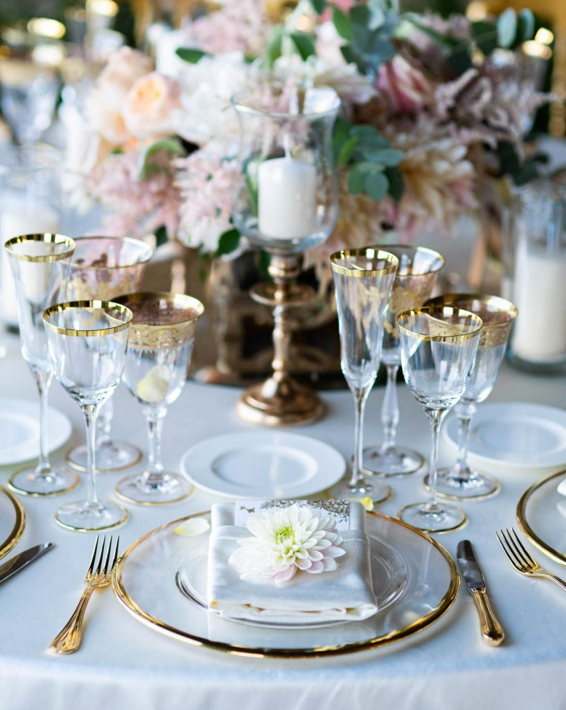 Close up details of bridal table setting in white gold and crystal with candles and flowers at Villa Cimbrone in Ravello on the Amalfi Coast of Italy, planned by Brenda Babcock and shot by luxury wedding photographer Francesco Bognin