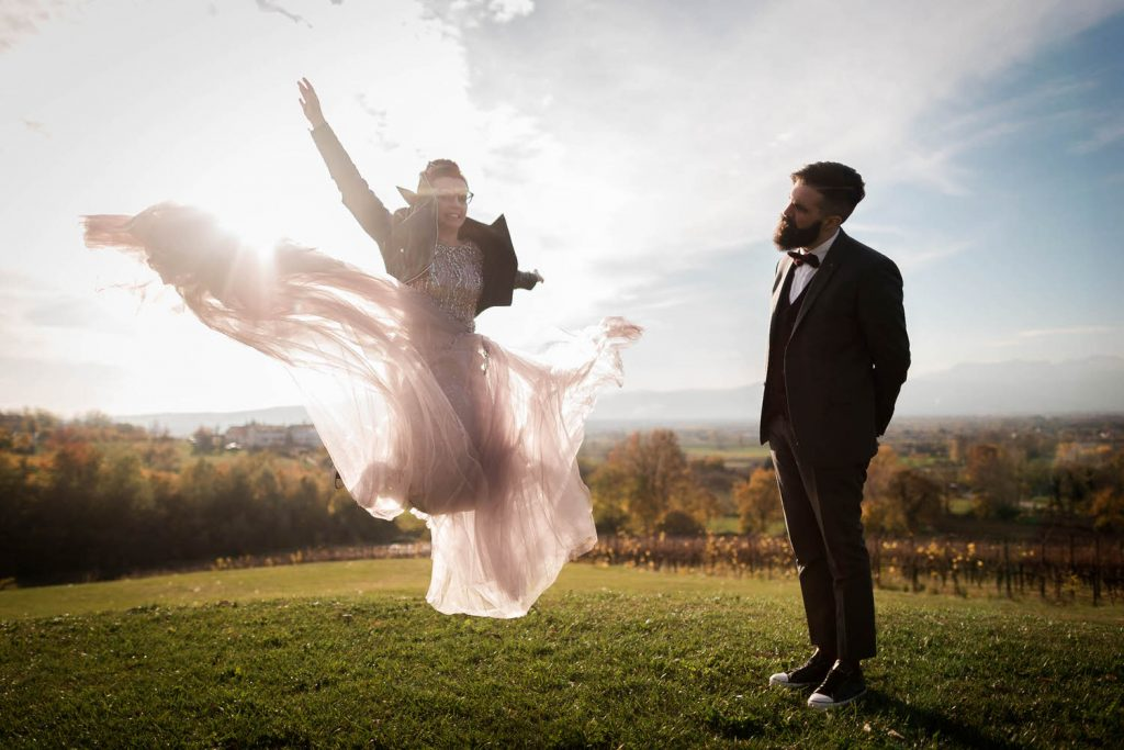 A bride jumps high in the air, her purple wedding dress flying in a glowing cloud around her as the sun shines from behind and her groom stands beside her with his head cocked in appreciation shot by luxury wedding photographer Francesco Bognin