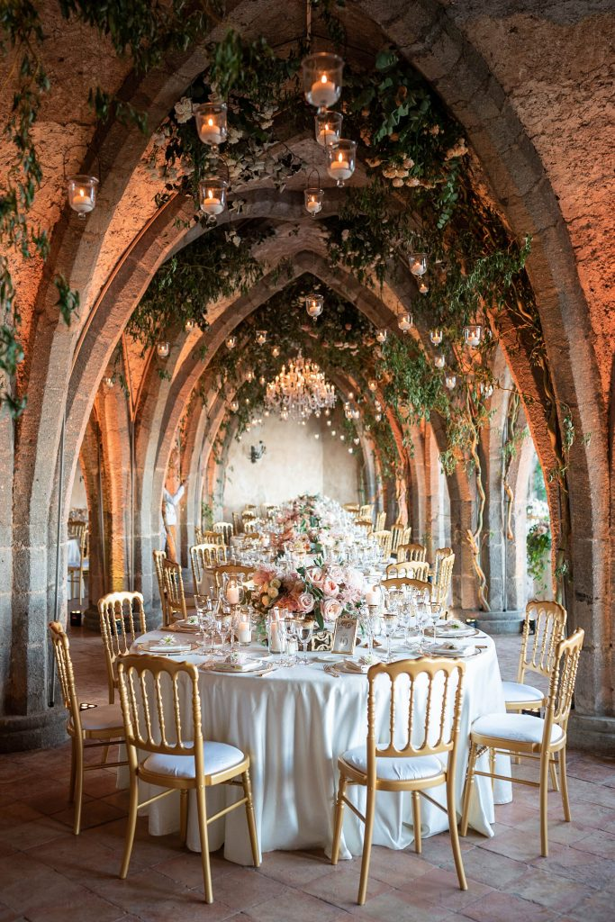 Close up details of bridal table setting in white gold and crystal with candles and flowers with candles and greenery overhead in the crypts of Villa Cimbrone in Ravello on the Amalfi Coast of Italy, planned by Brenda Babcock and shot by luxury wedding photographer Francesco Bognin