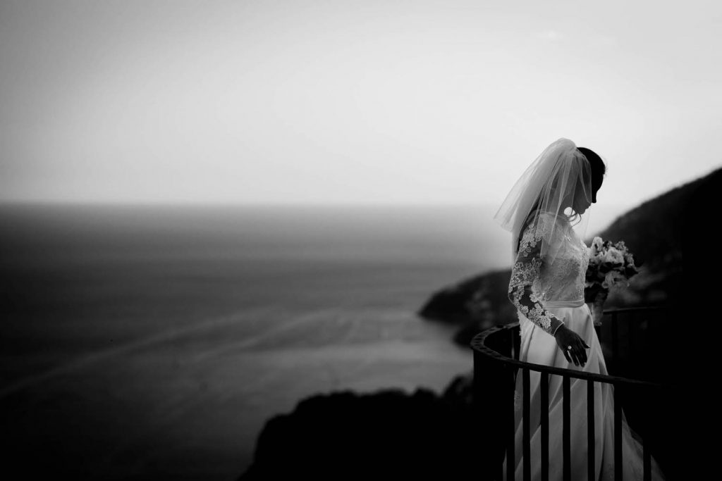 A black and white fine art profile portrait of a bride resting with her back against the sea and hills of the Amalfi coast in Ravello at Villa Cimbrone, planned by Barbara Babcock and shot by luxury wedding photographer Francesco Bognin