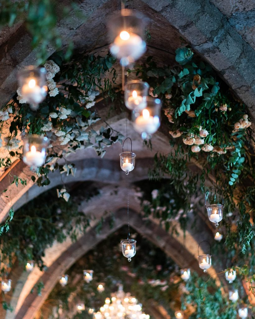 Overhead details of greenery and candles decorating the ceiling of the crypts of Villa Cimbrone in Ravello on the Amalfi Coast, planned by Brenda Babcock and shot by luxury wedding photographer Francesco Bognin