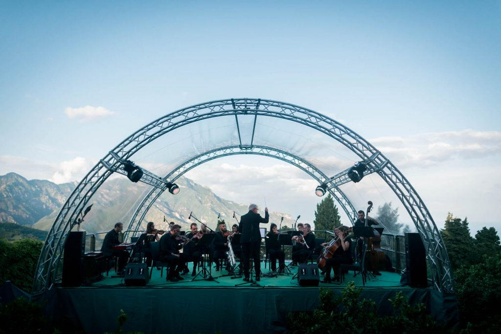 An elevated full orchestra plays under a transparent dome just outside of the crypts of Villa Cimbrone in Ravello with the hills of the Amalfi coast in the background, planned by Brenda Babcock and shot luxury wedding photographer Francesco Bognin