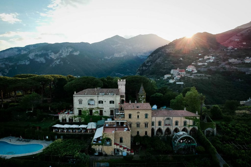 An Aerial drone photo of Villa Cimbrone, nestled in the hills of the Amalfi coast and with the sunset shining from behind. Planned by Brenda Babcock and shot by luxury wedding and drone photographer Francesco Bognin