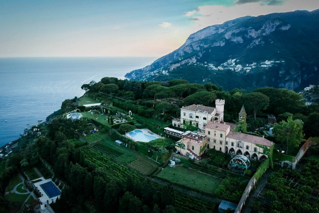 An Aerial drone photo of Villa Cimbrone, nestled in the hills and against the sea of the Amalfi coast and with the sunset shining from behind. Planned by Brenda Babcock and shot by luxury wedding and drone photographer Francesco Bognin