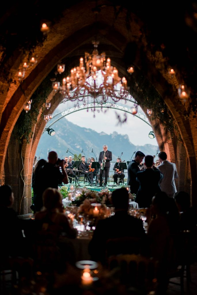 A full orchestra visible from the crypts of Villa cimbrone, with silhouettes of guests and glowing candles in the foreground, planned by Brenda Babcock and shot by luxury wedding photographer Francesco Bognin
